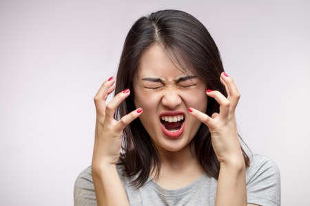 Isolated studio shot of furious Asian young wife screams desperately, being angry, irritated and aggressive while quarelling with her husband. Negative Human emotions Concept