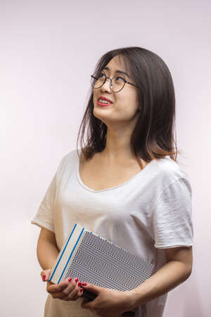 Asian cheerful student female wearing spectacles, dressed in loose white t-shirt reading interesting and funny book on white background isolated at studio