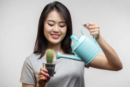 Asian attractive happy female model watering little green cactus in flowerpot by small blue watering can, symbolizing dry skin or hair need water, Moisturizing Skin and Hair Ritual Concet Banco de Imagens