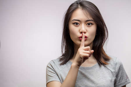 Asian female model keeping index finger near mouth making hush sign. Closeup portrait of young Korean woman demands silence, respecting woman s secret