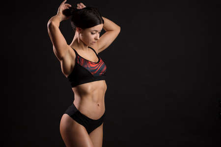 Perfect trained body Concept. Studio shot of stunning hot sporty fitness woman dressed in sportive bra and pants against black wall with copyspace. Fitness, Gym, SportsWear Concept. Standard-Bild