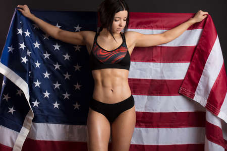 Woman bodybuilder rising freely American flag, concept of power and strength.