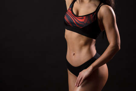 Midsection studio portrait of bodybuilder female six-pack. Bodybuilder female with flat trained belly over black background