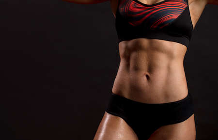 Close up of fit female abs isolated on black background with copy space. Fitness female and trained stomach, Perfect Slim Body. Sport, Bodybuilding, Fitness Concept Standard-Bild