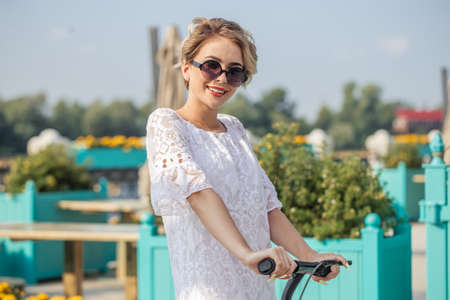 woman in sunglasses with kick scooter on beautiful day enjoying. Portrait of girl using technology