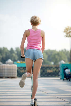 back view of blonde woman in pink top and jeans shorts riding on blue kick scooter, buttock and legs