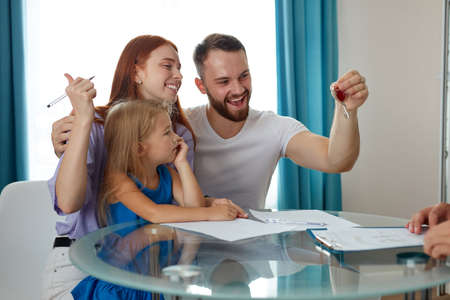 happy male with wife and daughter get keys from their first house, they sit excited, sign the documents to get mortgage Stock fotó