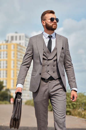 portrait of handsome caucasian businessman with bag going at business meeting, in formal suit outdoors
