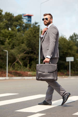caucasian businessman commuting to office carrying his office bag, handsome male in formal clothes walking on street to office, cross city streets