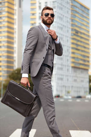 side view on caucasian businessman in suit or tuxedo walking with bag in hands, wearing sunglasses. in city streets 免版税图像