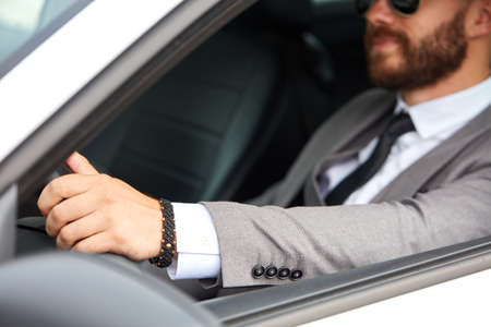 handsome caucasian businessman sits inside of representative luxurious car, confident male in formal wear