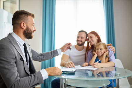 young caucasian family with child get keys from their first flat, house or apartment. happy owners sit together, get first property