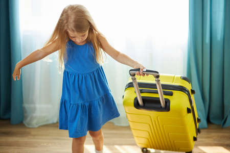 happy little caucasian child girl tourist packs clothes into a yellow suitcase for travel, vacation. alone in living room Imagens