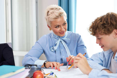 young blonde female tutor came to schoolboy at home, share knowledge, explain, teach all rules he needs for best marks in school Foto de archivo
