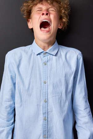 emotional caucasian teen boy is screaming, affective boy has an unstable psyche Archivio Fotografico