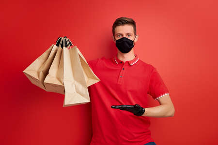 young caucasian delivery man employee in red t-shirt uniform and mask hold craft paper packet with food isolated over red background, service quarantine pandemic coronavirus concept