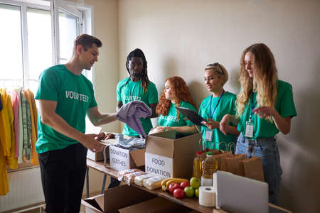 group of diverse people working in charitable foundation, happy caucasian and african volunteers looking at donation box, separating donations stuffs