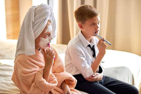 sleepy caucasian kids brushing teeth in the morning on bed, children preparing to go to work.