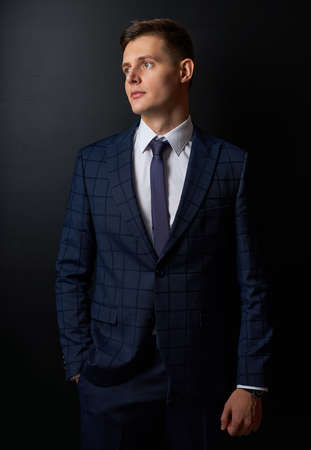 portrait of successful entrepreneur guy in classic tuxedo isolated on black background. young male posing, looking away