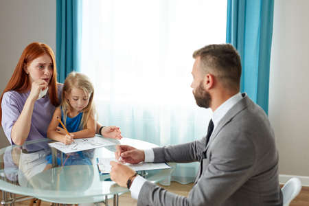 young depressed caucasian woman with child girl get support by psychologist, they sit at table talking, woman with red hair explain her problem and situation Stock Photo