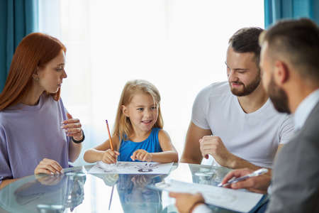 little caucasian daughter want parents to be together, she is drawing mom and dad on paper, family came to get psychological help and support, what they need to do