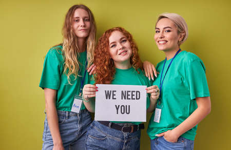 beautiful caucasian women waiting for merciful volunteers in their organization, they need active altruistic people, wearing green t-shirts, isolated over green background