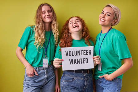 beautiful caucasian women waiting for merciful volunteers in their organization, they need active altruistic people, wearing green t-shirts, isolated over green background Stock Photo