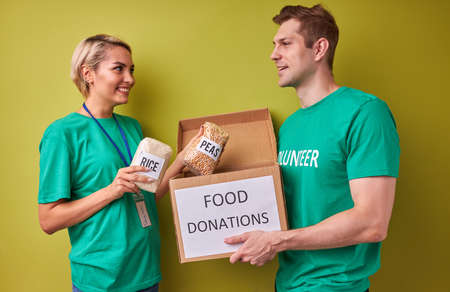 merciful volunteer put cereals in donation box, kind woman and man engaged in charity