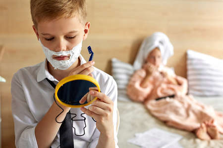 close-up portrait of child boy shaving beard, using small mirror. at home, his wife girl lying on bed in the background