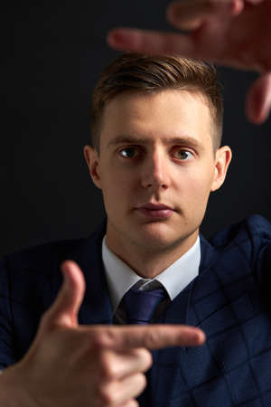 office worker in suit make a frame for a photo, look at camera posing isolated on black background