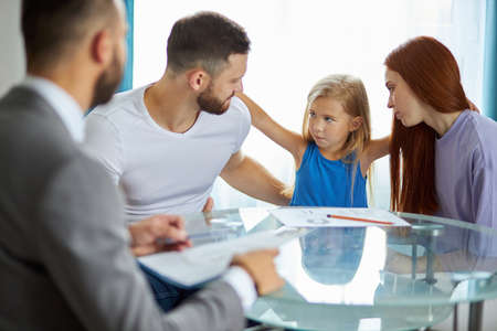 friendly caucasian male psychologist help family going to be divorced, try to eliminate potential psychological problems of child girl