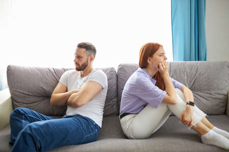 caucasian depressed redhead wife feeling upset after fight with husband, sit back to back. frustrated young girlfriend and boyfriend avoiding talk, couple tired of bad relationships, sit on sofa