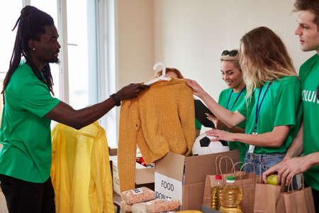 young multi-ethnic group of people gathered for charity, kind men and women in green t-shirt have cardboard boxes with clothes and food, want to help poor people