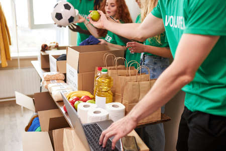 group of diverse people sort through donated food items while volunteering in community, they use cardboard boxes for collecting donation