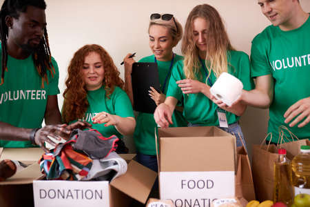 young enthusiastic volunteers with donations for poor people, cardboard box with clothes for charity. kind people help poor, cases full of clothing for poor giving, social activity concept