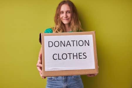 portrait of caucasian young woman holding box donation clothes, help poor people, isolated green background Reklamní fotografie