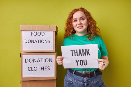adorable caucasian red haired woman say thanks to kind people, volunteers, look at camera, stand next to boxes with donation clothes and food Reklamní fotografie