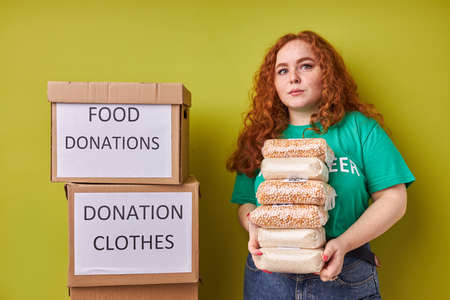 beautiful redhead volunteer woman collecting donation for poor, young girl with carboard boxes smiles at camera, isolated green background Reklamní fotografie