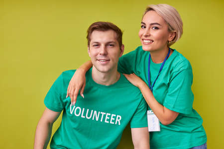 friendly man and woman keen on charity, caucasian friends in green t-shirts look at camera and smile, volunteering