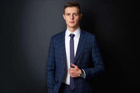 attractive caucasian man in formal stylish suit posing at camera isolated on black background, confident business person