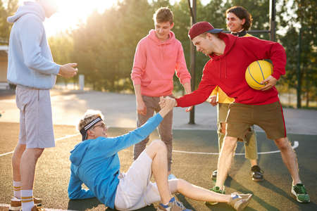buddies reach out to a fallen friend at basketball court, caucasian young guys play basketball games