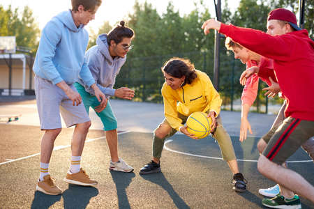 basketball players outdoors. summer vacation, holidays, games and friendship concept. caucasian teenagers in casual hoodies engaged in sport, healthy lifestyle, youth concept