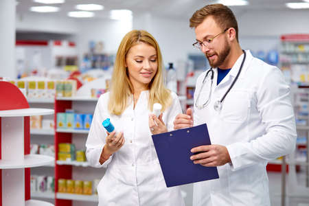 two young caucasian colleagues in white medical gown pharmacists fulfilling a prescription holding medication in hand, checking the script