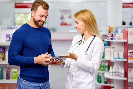 male customer having a discrete talk with druggist in pharmacy, ask for advice, pharmacist woman help, ask for symptoms 版權商用圖片
