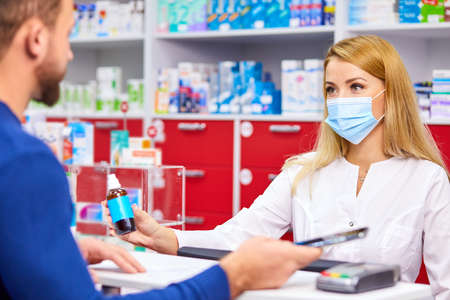 young female apothecary with drug and male customer at pharmacy, help, consult. medicine, pharmaceutics, healthcare and people concept