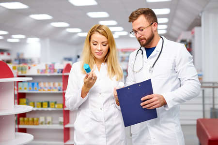 appealing two caucasian pharmacists communicating while supervising medical products, they have talk, checking digital tablet