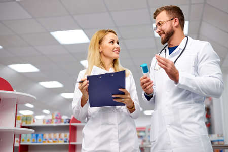 team of young caucasian chemists or druggists discussing medicines, check medical indications, in white medical gowns, at work place 版權商用圖片