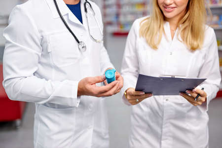 two young caucasian pharmacists are discussing medication, using a digital tablet and documents. man and woman in white medical gown working in pharmacy