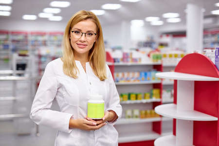 good-looking apothecary recommends the drug for treatment, hold medicament in hands and look at camera, pharmacy in the background 版權商用圖片