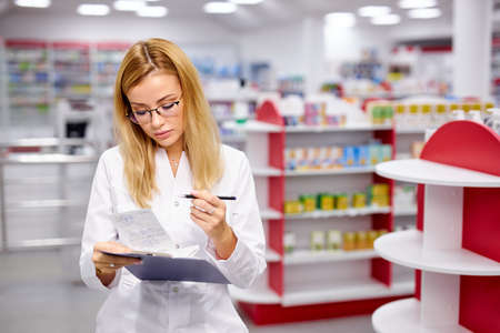 young good-looking woman pharmacist searching for medication on pharmacy shelves, examine and check assortment of drugs in pharmacy 版權商用圖片